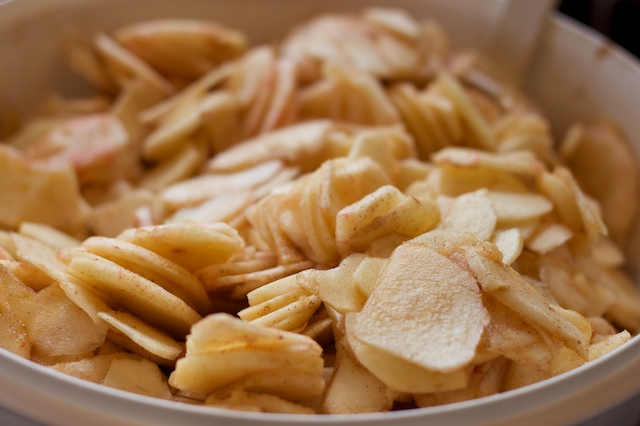 Sliced apples mixed with sugar, lemon juice, nutmeg, cinnamon & flour.